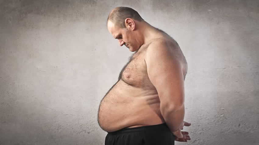 Overweight man with sleep apnea looking at his excessive weight gain